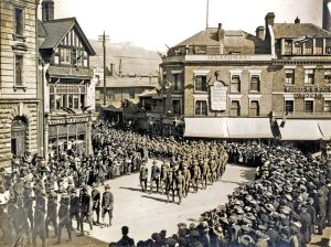 Soldiers marching through Market Square during World War I. The photograph shows the north and east of the Square with Castle Street and the Castle beyond. Dover Museum