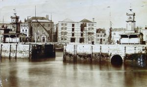 The entrance into the Bason, later the Granville Dock, with Custom House Quay at the rear. On the facing left side of the entrance was a tower containing a large compass and on the right, the red face with a white rim clock tower that Dickens talks about in Out of Season. Dover Library