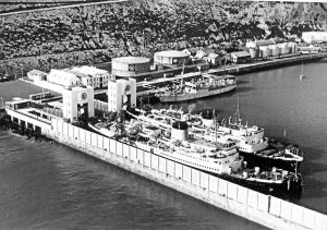 Ariel cable ship in the Camber 1959 in front of the two oil tanks the offices are to the left. The two cross Channel ships are Maid of Kent nearest the quay and the Lord Warden on the outside. Dover Harbour Board
