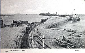 Admiralty Pier during the construction of the extension with the former SER railway line going west and the former LCDR line going north. A steamer can be seen tied up against the outside of the Pier and boat builders on Shakespeare Beach Dover Library