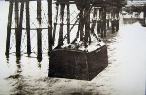 Diving bell with the men who worked inside to prepare the sea bed being lowered into the sea by a crane . Dover Transport Museum
