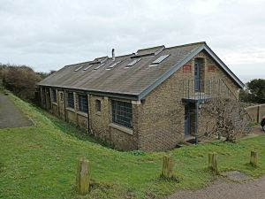 One of the two former Prison buildings at Langdon Cliff that are still standing. The plaques give date of construction in 1902 and refurbishment in 1995. A Sencicle