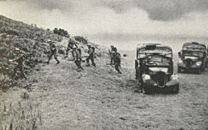 Royal Army Service Corps and members of the Home Guard searching the vegetation along a Southern English beach for enemy paratroops - government leaflet. Doyle Collection