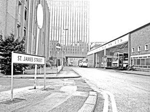 "EKRCC bus garage in St James Street in this photograph is taken from Russell Street looking west. The back of Holiday Inn on Townwall Street and facing the sea, is on the left. <a href=""https://doverhistorian.com/2014/07/05/burlington-house-a-monument-to-an-arrogant-establishment/"">Burlington House</a> ahead showing the arch over St James Street that led out to the one way King Street. Buses on leaving the garage would turn left on to St James Street and then right onto the one way Russell Street. On arrival they would leave Townwall Street turn into Mill Lane and then left again into St James Street as can be seen by the coach in the photograph. On leaving the bus garage they would turn left onto St James Street and then onto the one way Russell Street that would take them to Townwall Street. At that time they could turn right into St James Street but due to the one way system would have to turn right again on to Dolphin Lane - at the back of the bus garage - from where they could reach the one way Russell Street. They would again turn right until they reached the two way Townwall Street. c1975. The photograph has been provided by Dover Museum"
