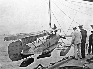 Short Folder seaplane (S.64), serial number 81, being hoisted out from the Royal Navy ship Hermes with wings folded. wikimedia commons
