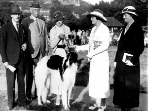 Annual Dog show on Pencester Gardens organised by the Dover Brotherhood and Sisterhood. Lady Anne Davenport presenting the 'Davenport Cup' for the best dog in show to Mrs C.A. Jenkins of Folkestone. Left to right, Mr A. Maxfield (Judge), Sir Henry Davenport (1866-1941), Mrs Jenkins, Lady Anne and Mrs Llewellyn Langley. The Winning dog was a black and white Borzoi, name not given.
