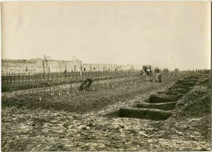 An American cemetery north of Toul, France 1918. Wooden crosses are grave markers, on the freshly-dug graves, with filled-in graves on the left. In the center are Troops completing the burials. Henry L. Graves. State Archives of North Carolina